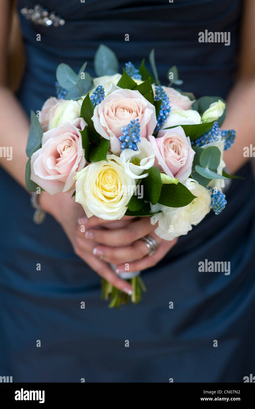 woman in a blue dress holding a bouquet of spring flowers including roses, muscari and ranunculus - Stock Image