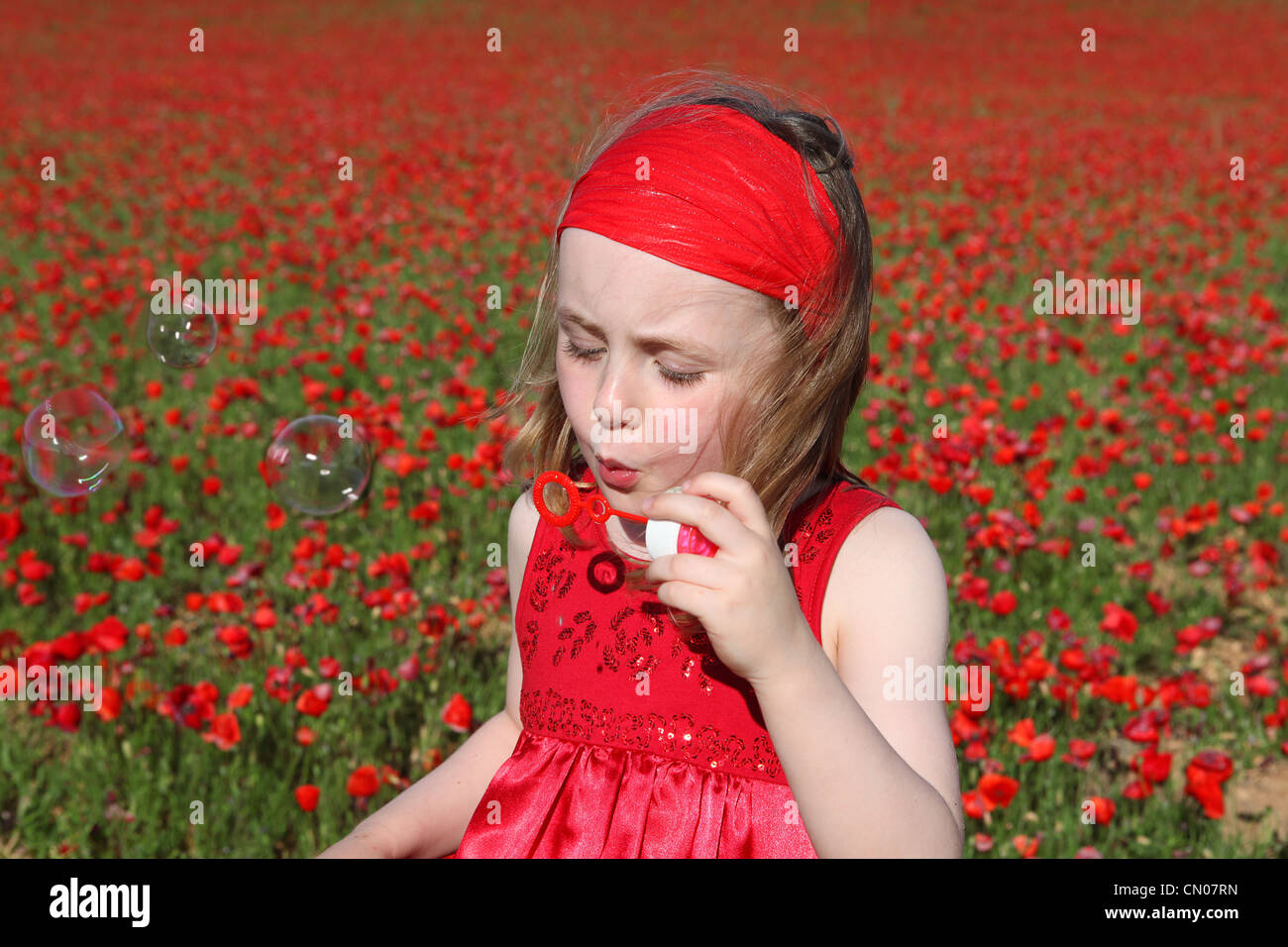 little girl blowing bubbles playing outdoors in summer Stock Photo