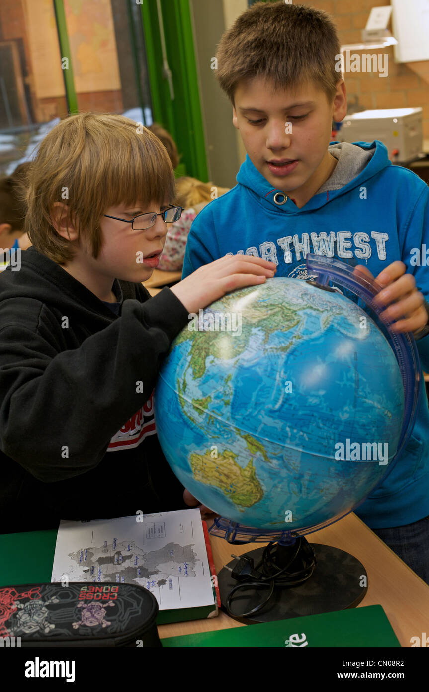 Schoolchildren studying a globe during a geography lesson in Germany - Stock Image