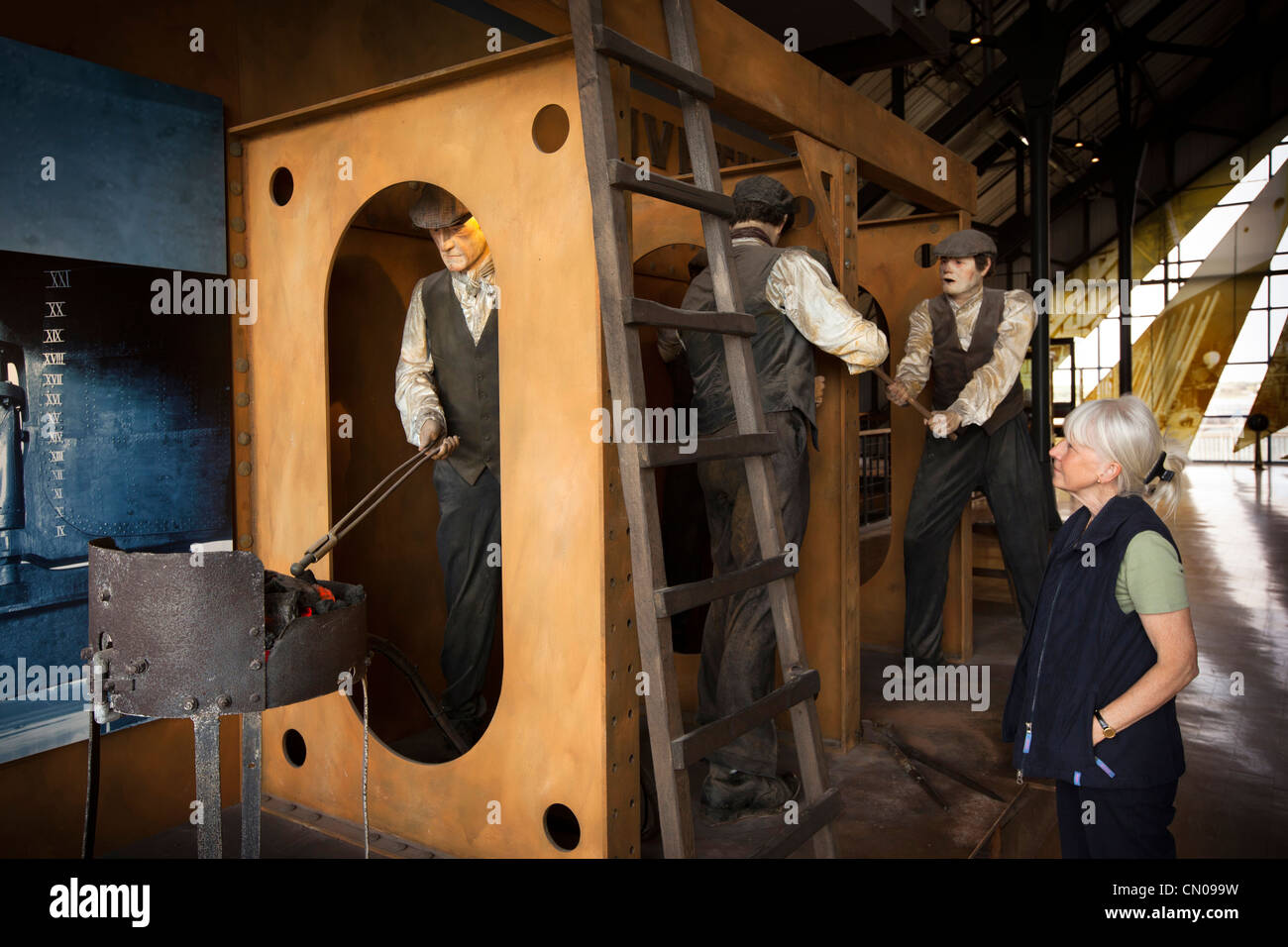 UK, Cumbria, Barrow in Furness, Dock Museum, shipbuilding exhibition, female visitor looking at riveting tableau - Stock Image