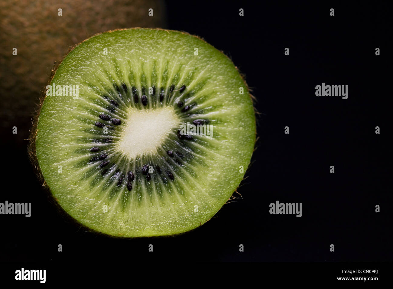 Actinidia deliciosa. Kiwi fruit cross section against a black background. - Stock Image