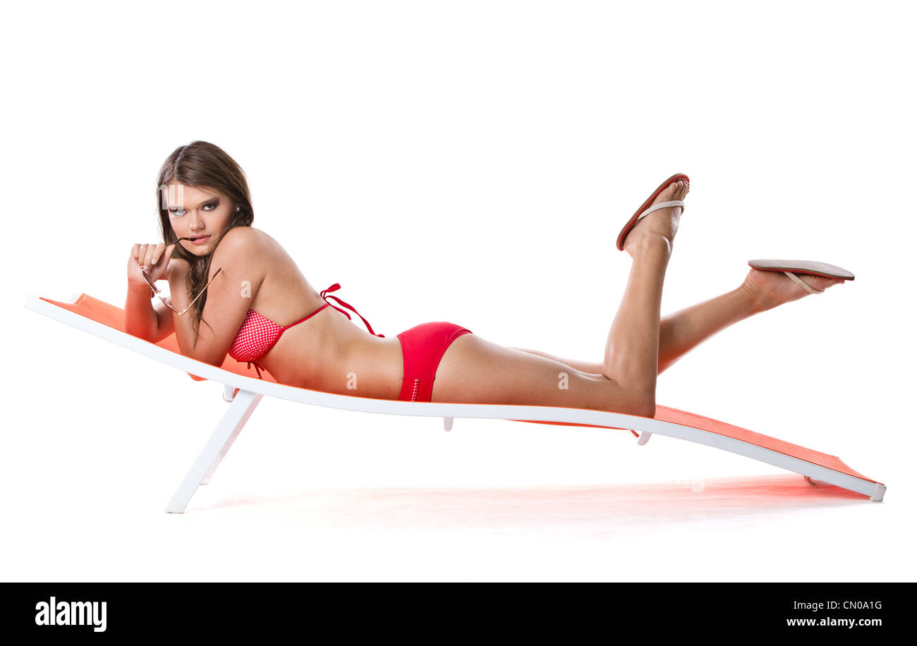 Beautiful young brunette woman relaxing on sunbed, vacation concept shot - Stock Image