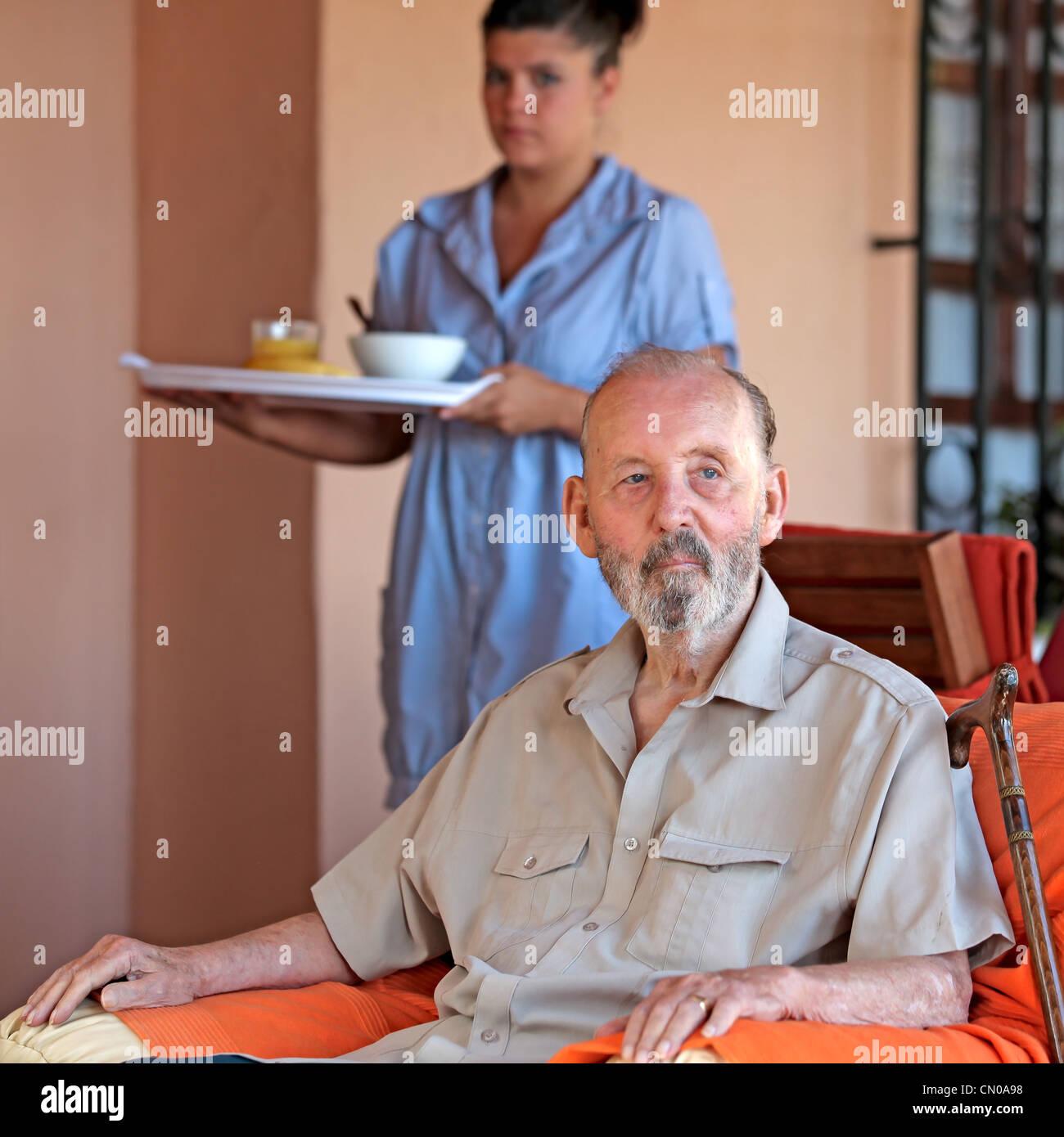 senior with carer or nurse bringing meal - Stock Image