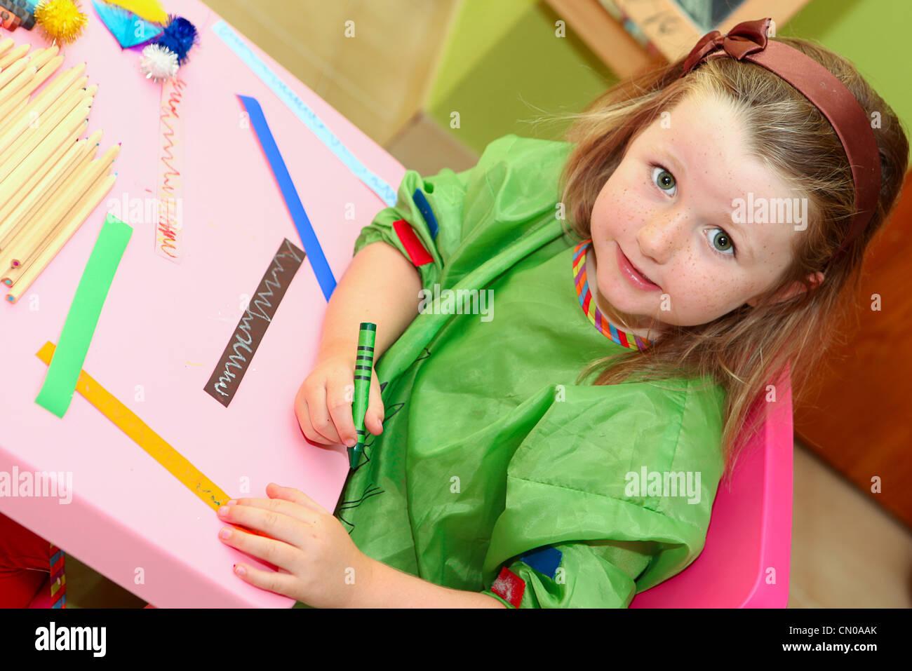 happy smiling kid drawing at home or school kindergarden or kindergarten - Stock Image