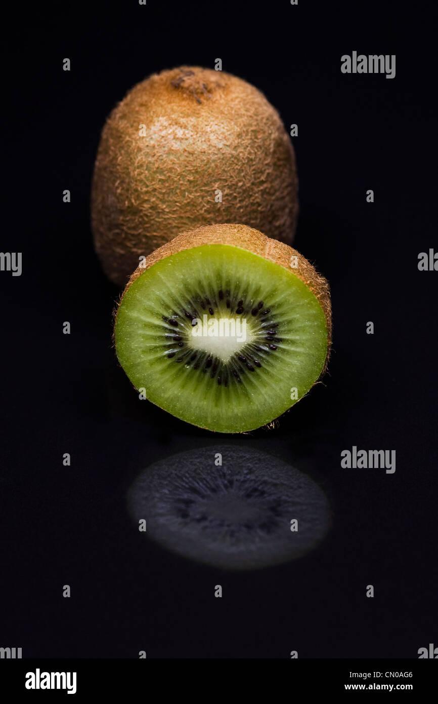 Actinidia deliciosa. Kiwi fruit against a black background. Chinese gooseberry. - Stock Image
