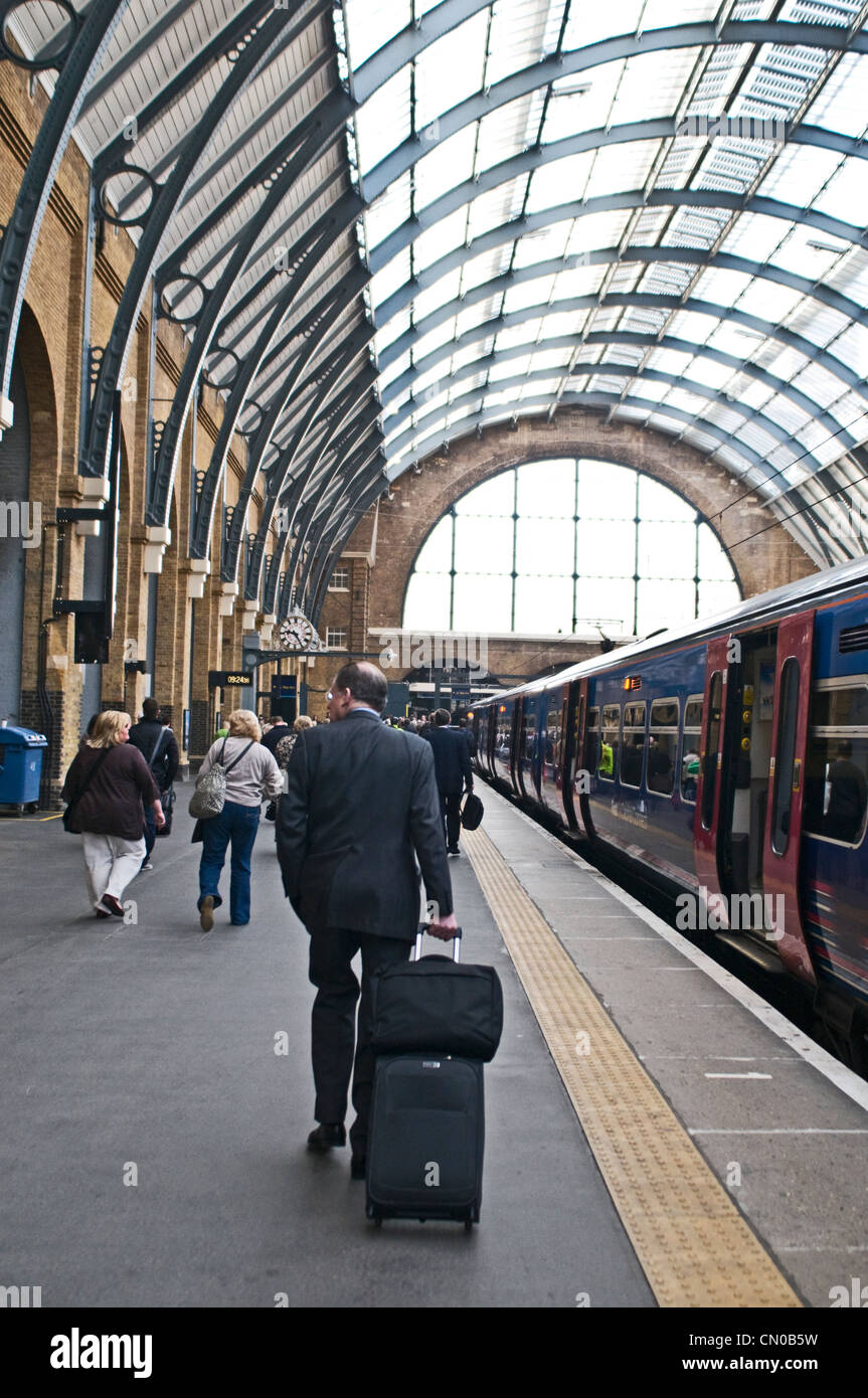 A business walking down the platform at London's Kings Cross train station, UK. - Stock Image