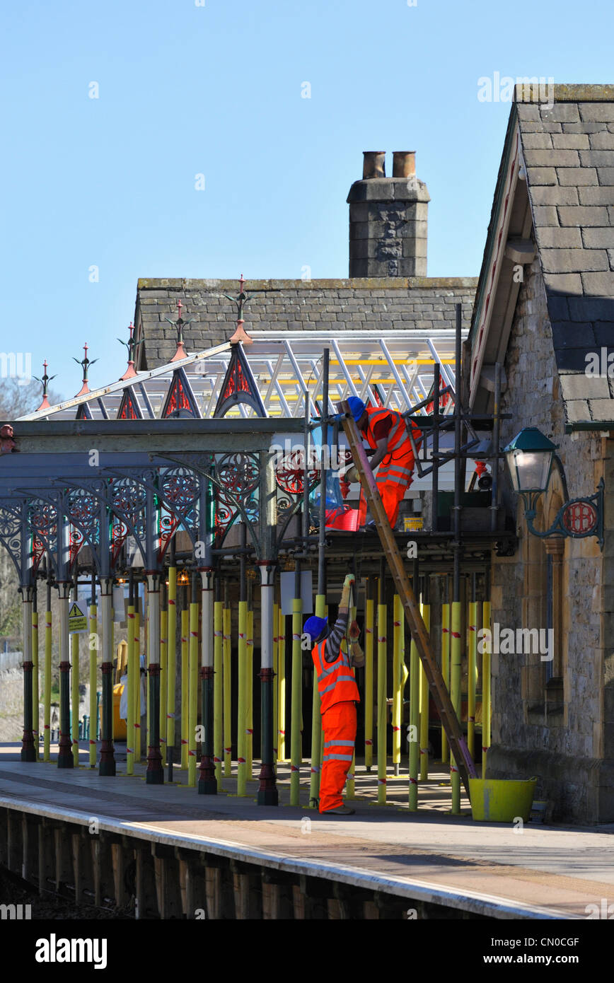 Workmen carrying out refurbishment work on rail station. Grange-over-Sands, Cumbria, England, United Kingdom, Europe. - Stock Image