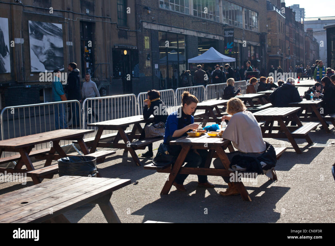 people sitting at picnic tables at an outdoor café in spitafield