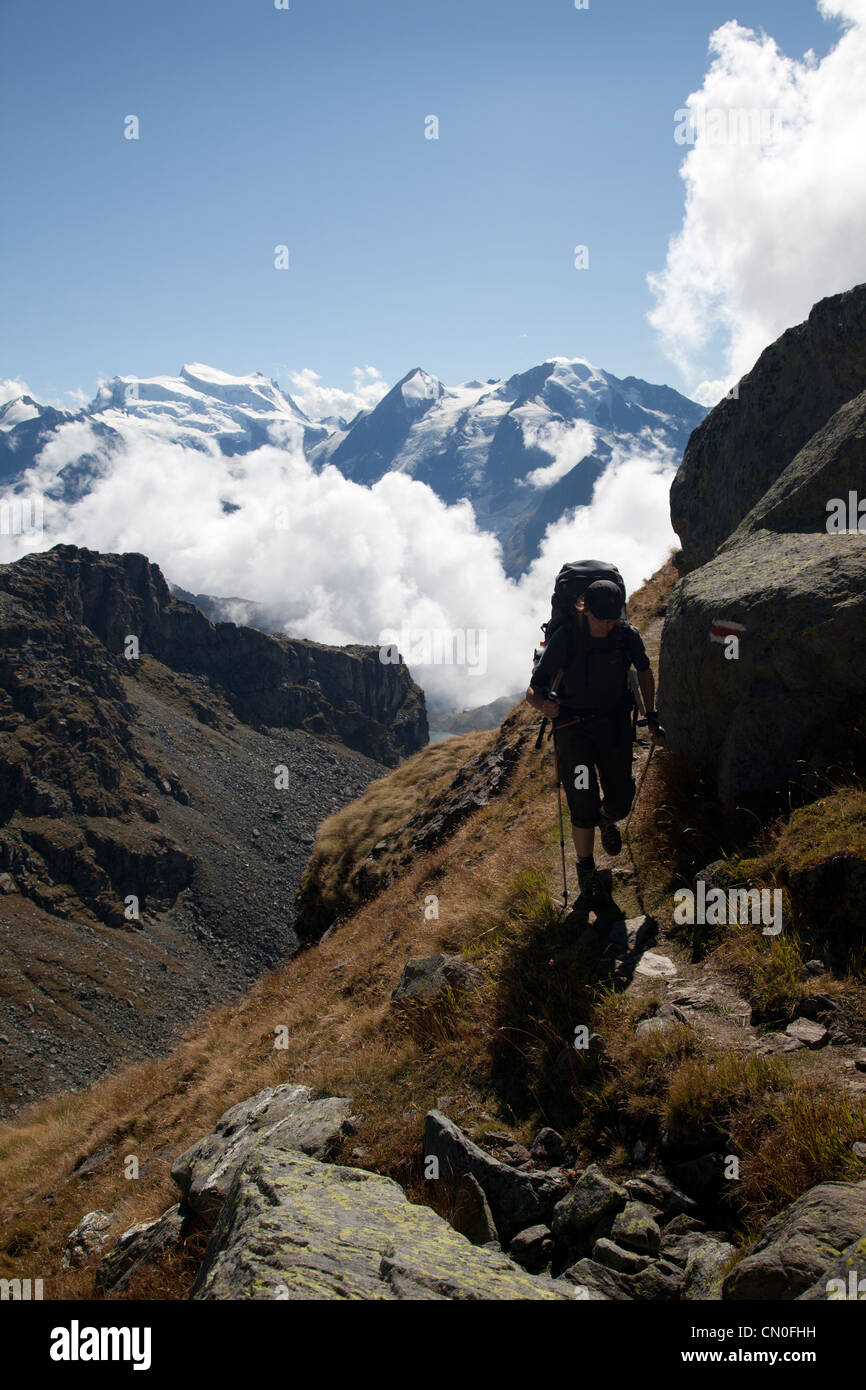 Walker on Haute Route with Haute Route signage (red and white stripes) with backdrop of Grand Combin. - Stock Image