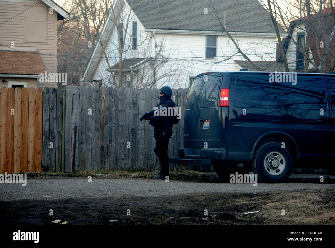 Swat officer,secures back entrance,during a drug raid,fully equipped with weapons. Stock Photo