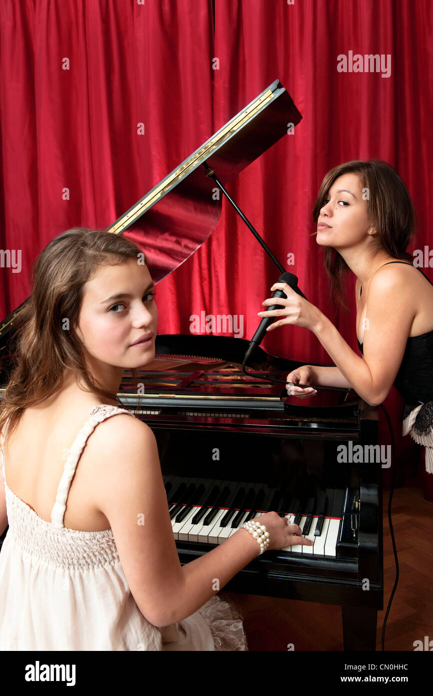 Two young women performing a piano recital, accompanied by vocals on a stage in front of a red curtain. - Stock Image