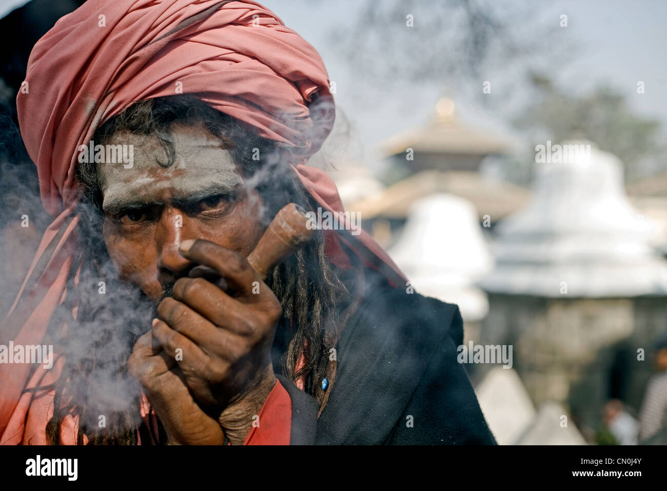 Sadhu smoking chilum (clay pipe ) during Shivaratri festival at Pashupatinath , Kathmandu , Nepal - Stock Image