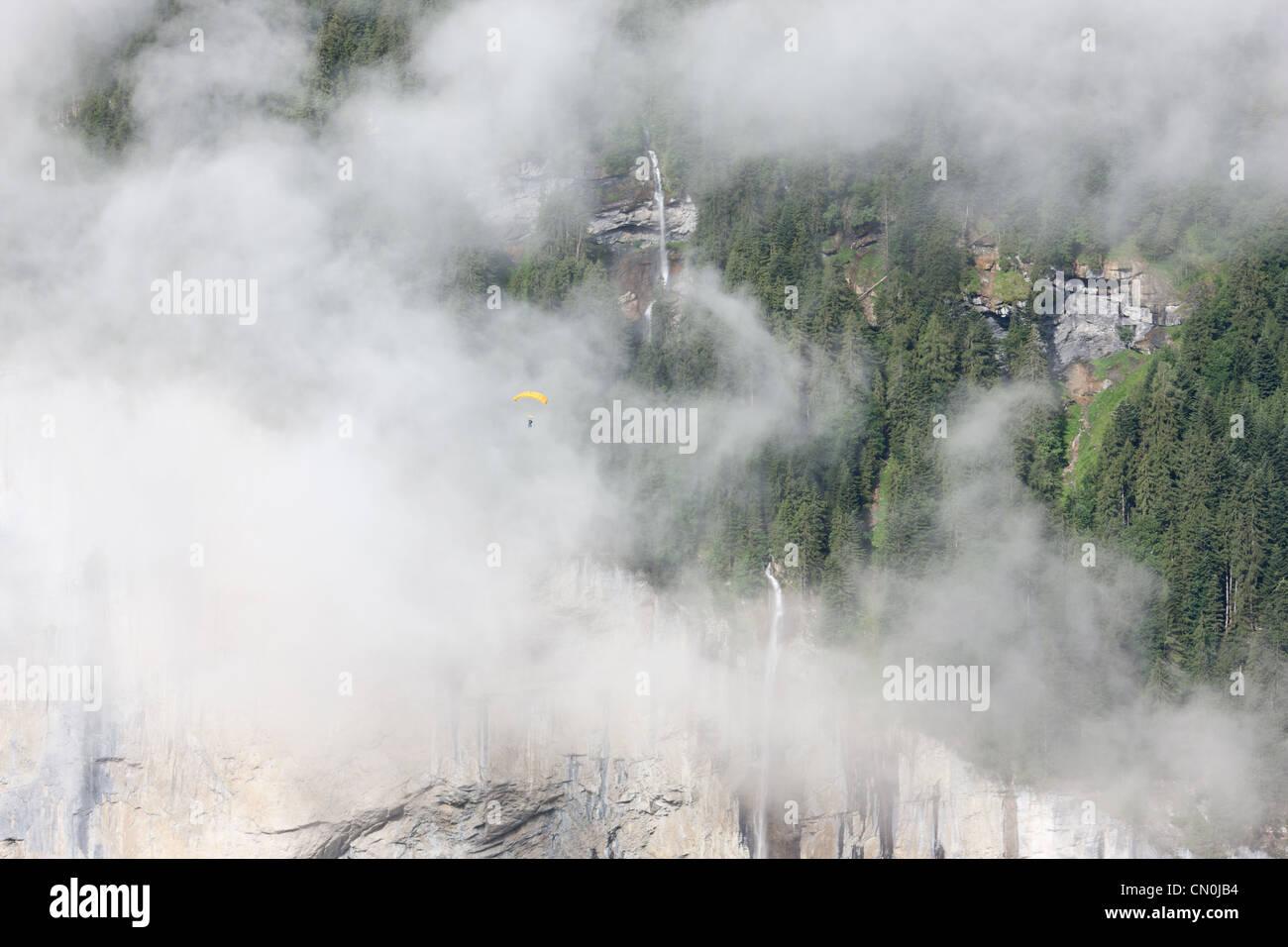SKYDIVER / PARACHUTIST soaring by the Staubbachfall over the Lauterbrunnen Valley, Bern, Switzerlland. - Stock Image