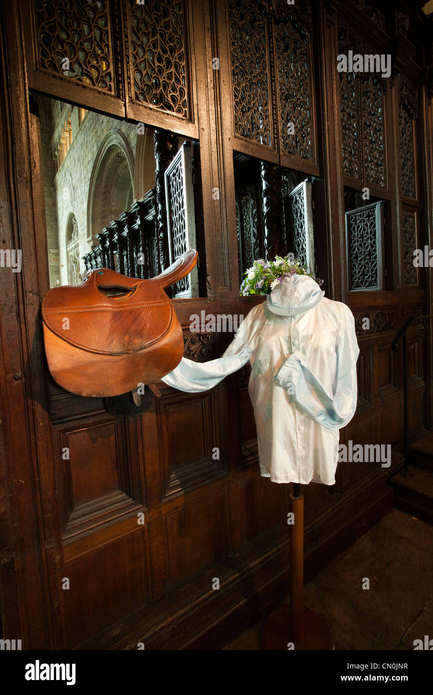 UK, Cumbria, Cartmel Priory interior, racing silks and saddle on Rood Screen during races - Stock Image