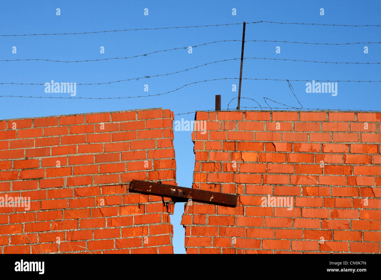 Red Brick broken Wall with barbed wire against blue sky - Stock Image