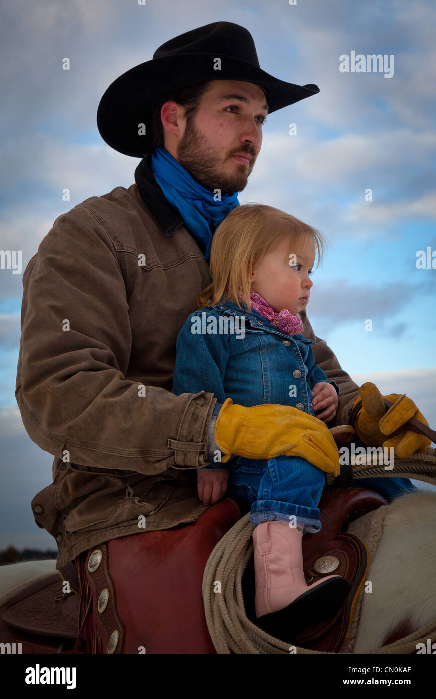 A cowboy and his daughter on horseback at ranch in northeastern Wyoming - Stock Image
