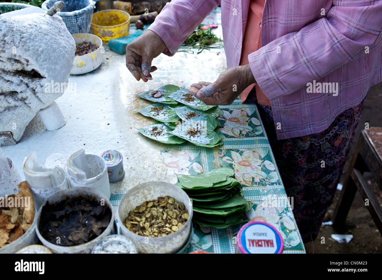 Burmese woman prepares betel leaf chews on the streets of Yangon (Rangoon), Myanmar (Burma) - Stock Image