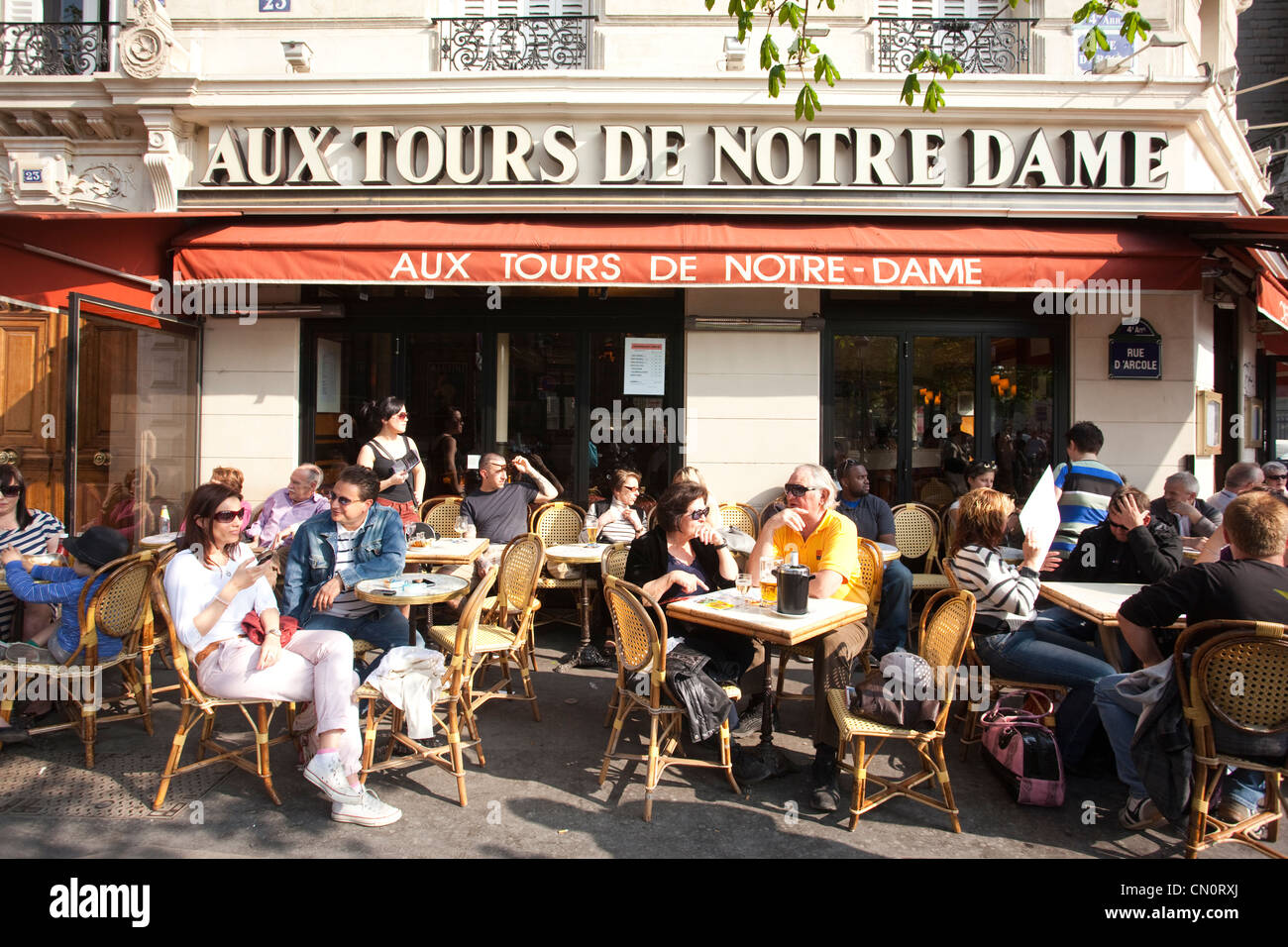 People sitting outside the Aux Tours de Notre Dame, brasserie on Rue d'Arcole, Paris, France - Stock Image