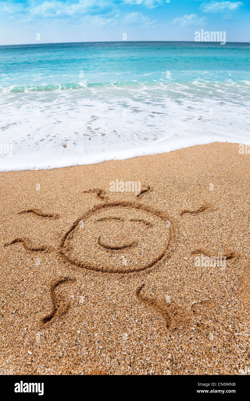 drawing smiling sun symbol on the beach - Stock Image