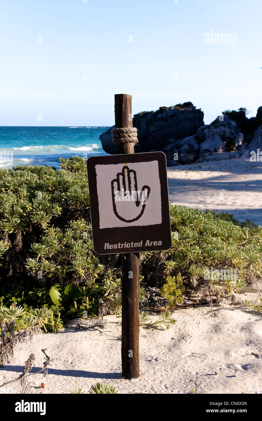 Sign denying access to a beautiful Caribbean beach (portrait format). - Stock Image