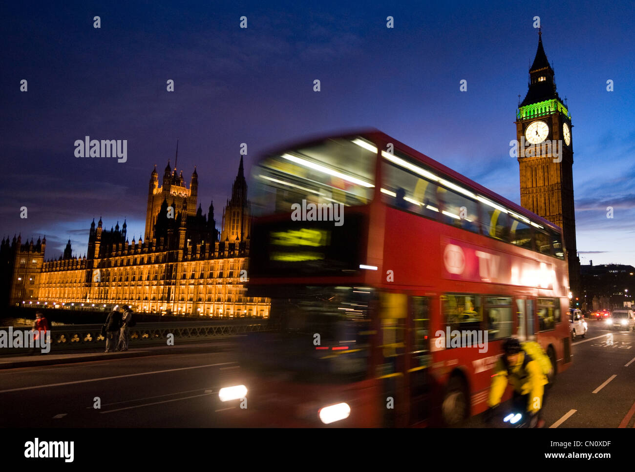 Double Decker bus and cyclist zoom past the Palace of Westminster (Big Ben) in London, England, on Nov. 4, 2009. - Stock Image