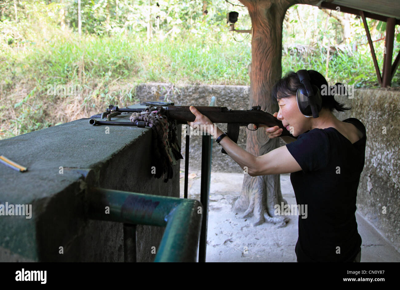 Tourist shooting live ammunition from a rifle, Tay Ninh Province,  Vietnam - Stock Image