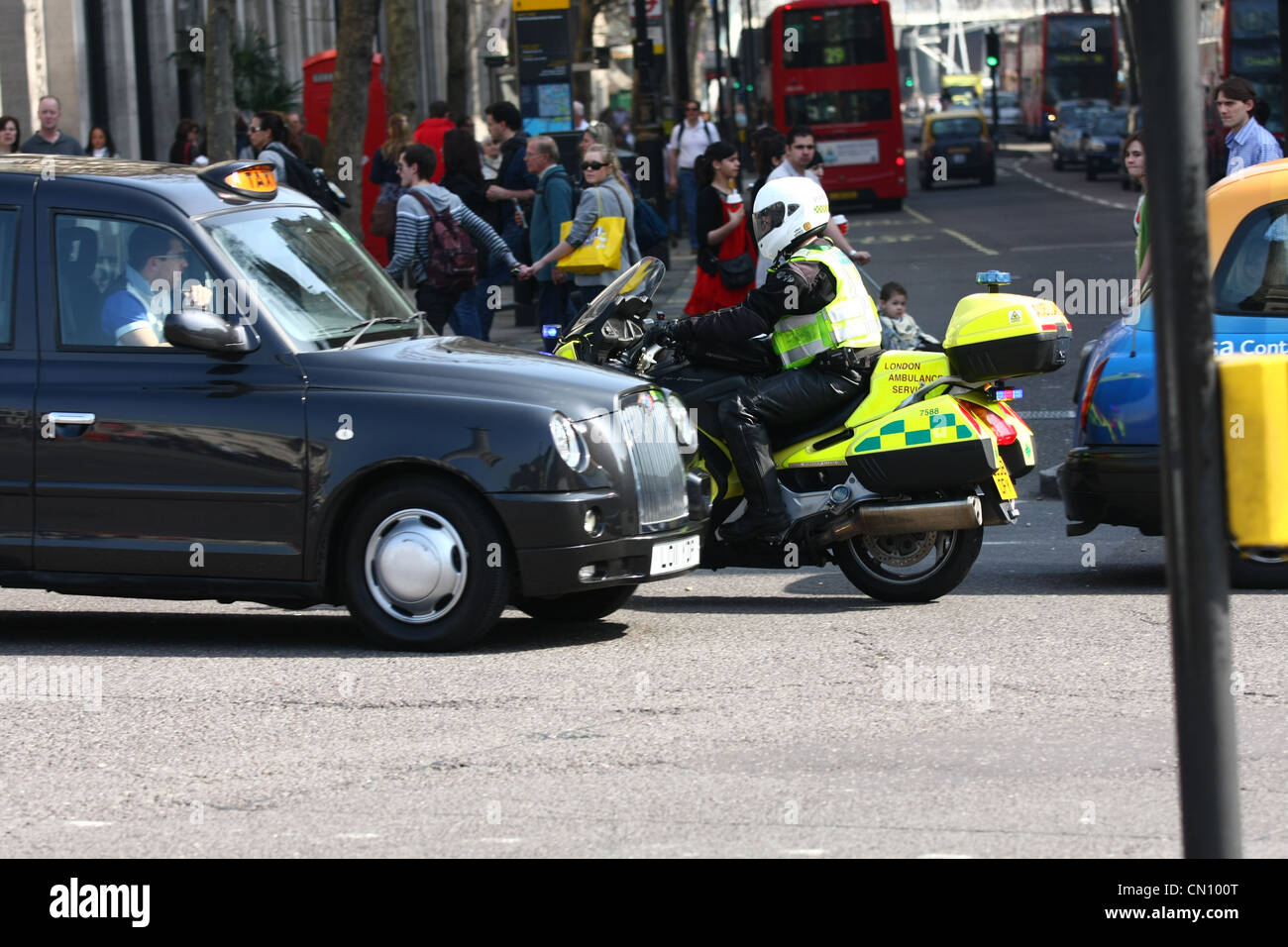 a London ambulance motorcyclist driving the wrong way around Trafalgar Square to get to an emergency - Stock Image