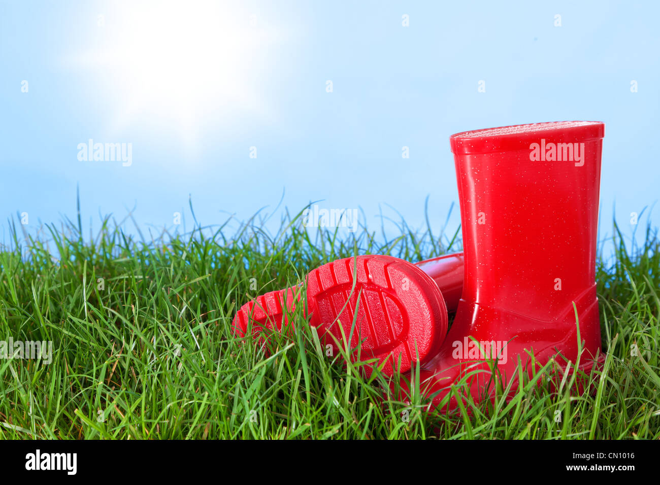Photo of a childs wellington boots on grass outside on a sunny day - Stock Image