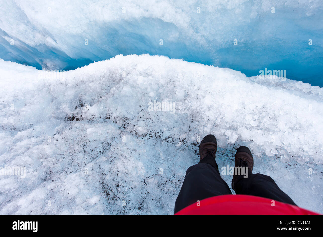 Standing on edge of a crevasse in Greenland - MR - Stock Image