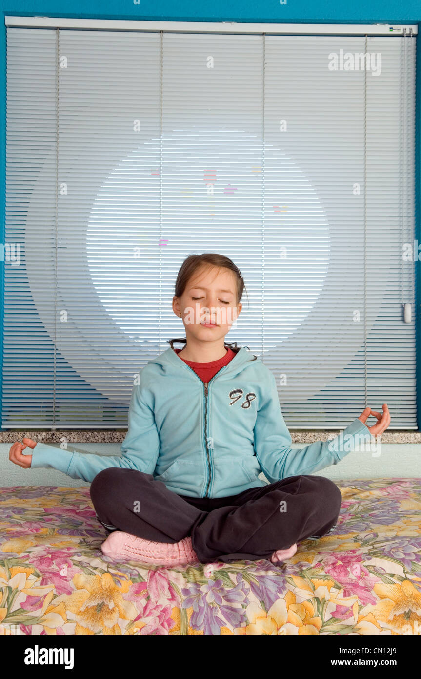 Young girl practising meditation in her room Stock Photo