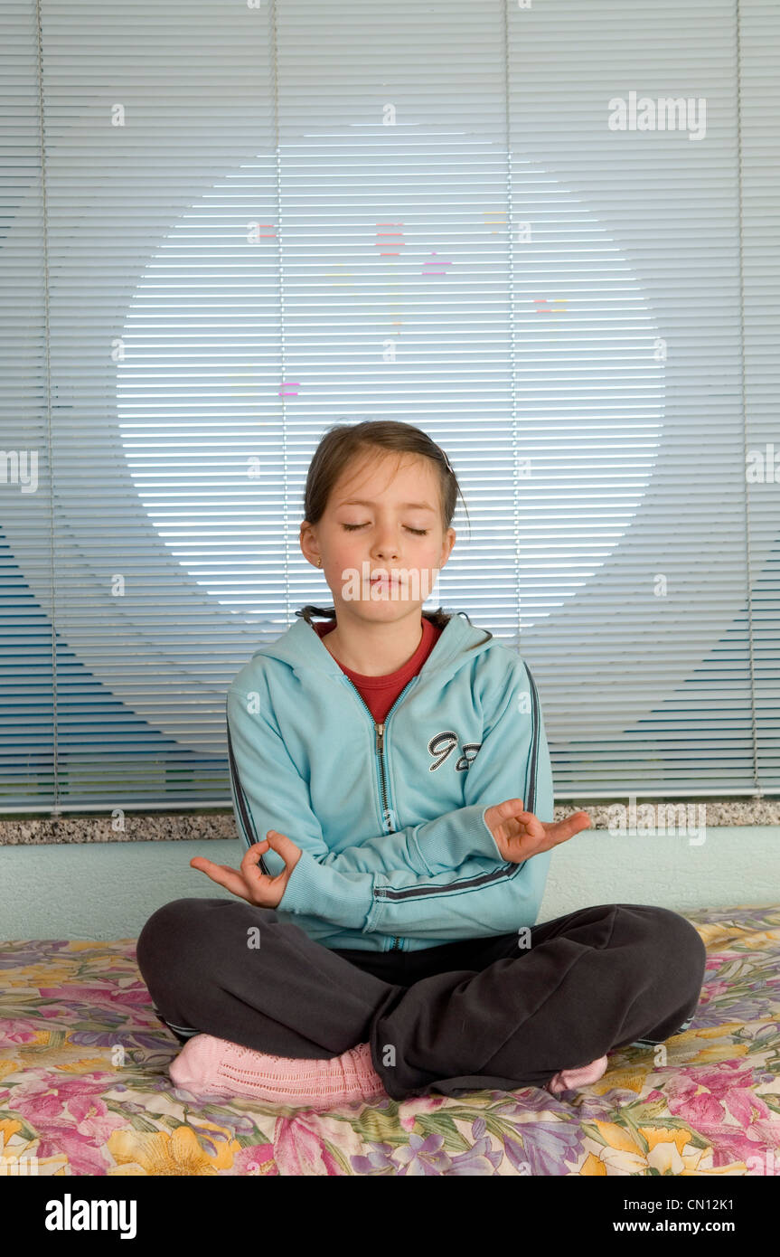 Young girl practising meditation in her room - Stock Image