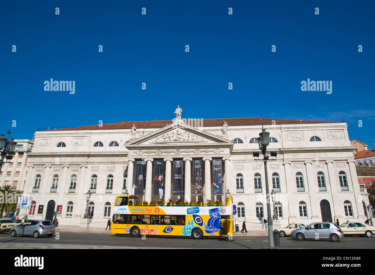 Sightseeing tour bus passing Teatro Nacional de Dona Maria II at Rossio square Lisbon Portugal Europe Stock Photo