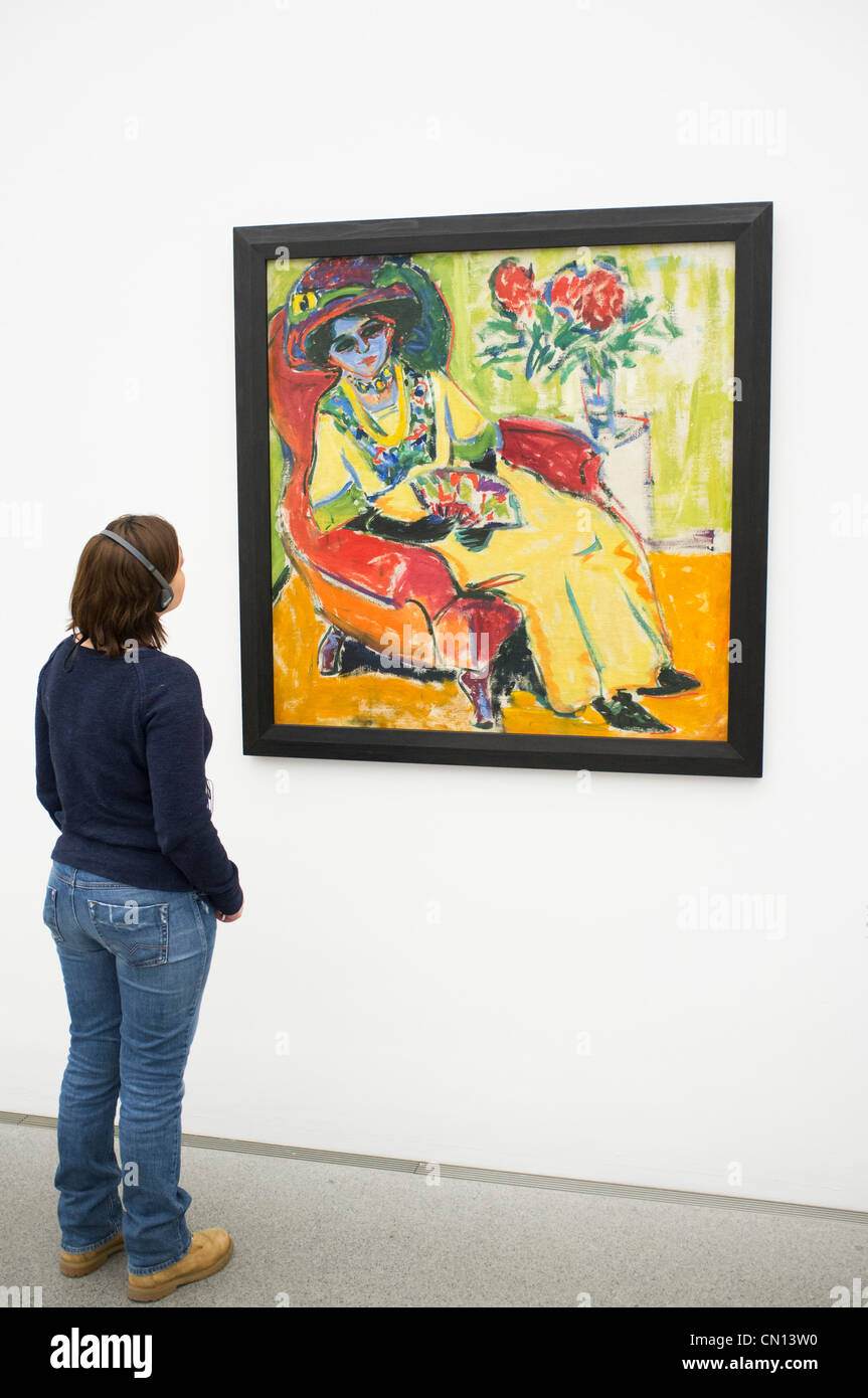 Woman looking at painting Bildnis Dodo by Ernst Ludwig Kirchner at Pinakothek Moderne art museum in Munich Germany - Stock Image