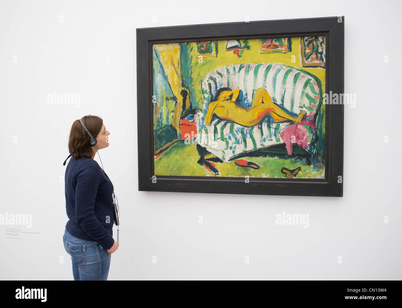 Woman looking at painting Liegendes Madchen by Erich Heckel at Pinakothek Moderne art museum in Munich Germany Stock Photo
