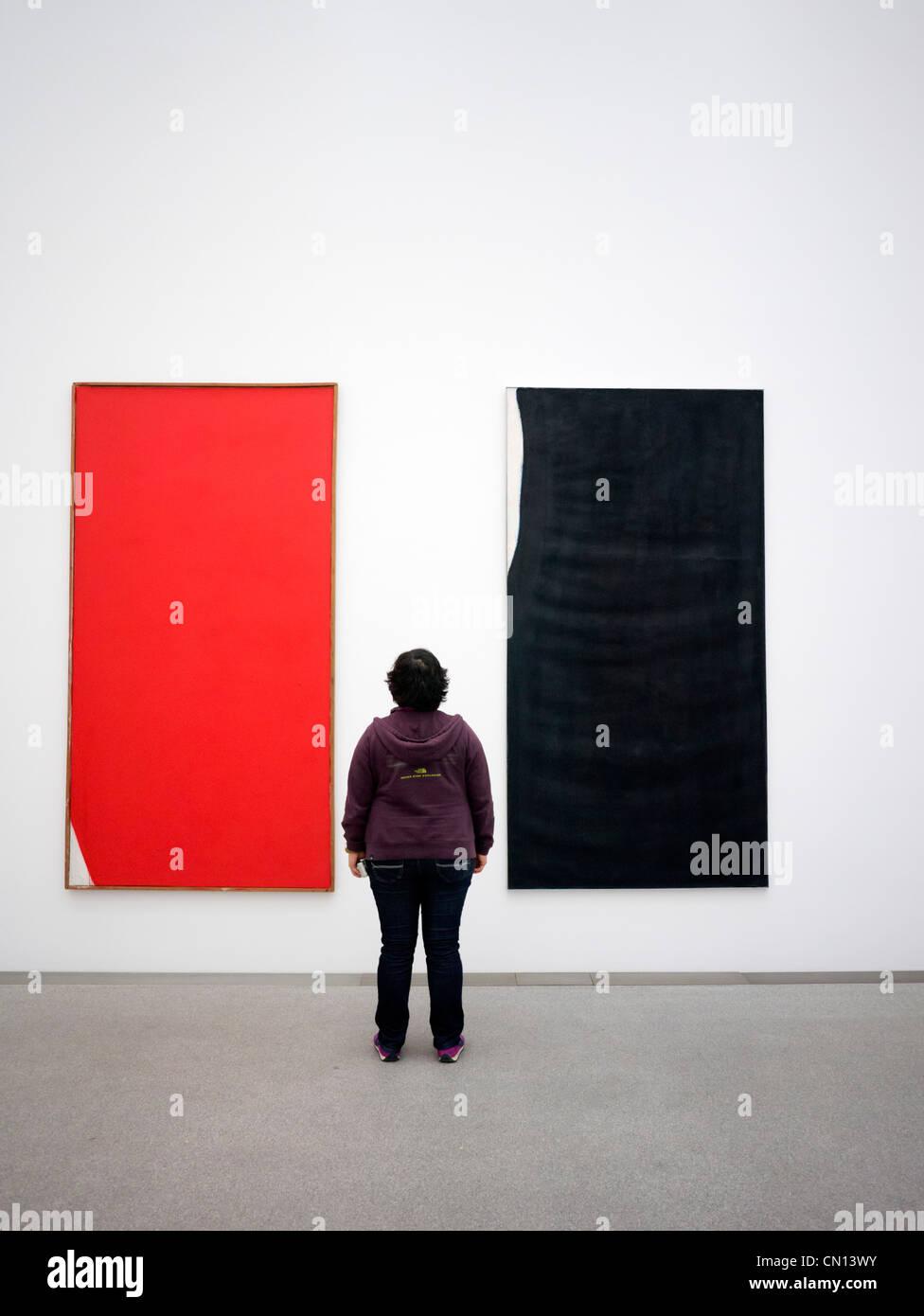 Woman looking at paintings Edles Eck and Ubermalung Blauschwarz by Arnulf Rainer at Pinakothek Moderne art museum Stock Photo