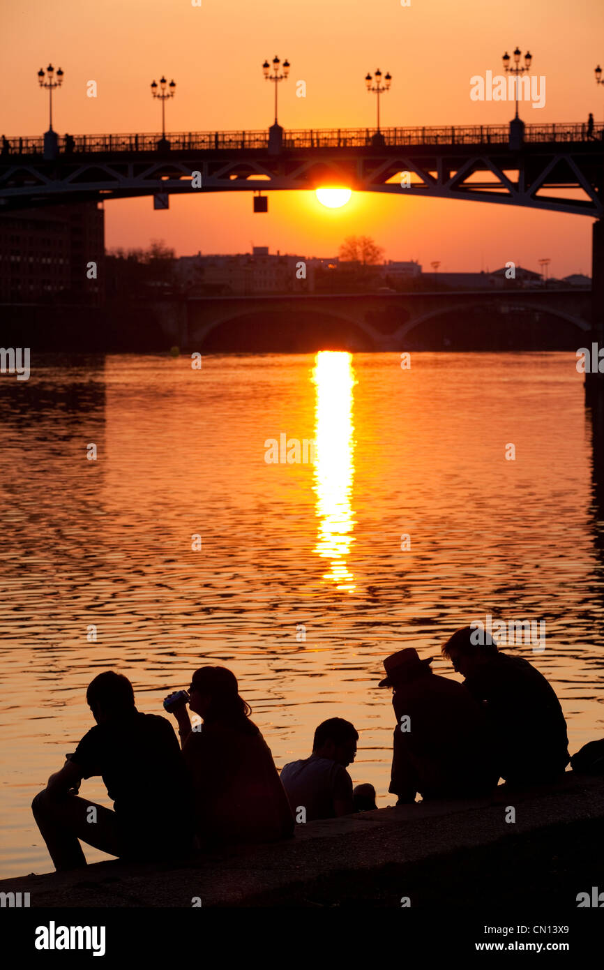 French people sat on the banks of La Garonne watching the  sunset behind the Pont St. Pierre, river Garonne, Toulouse, - Stock Image
