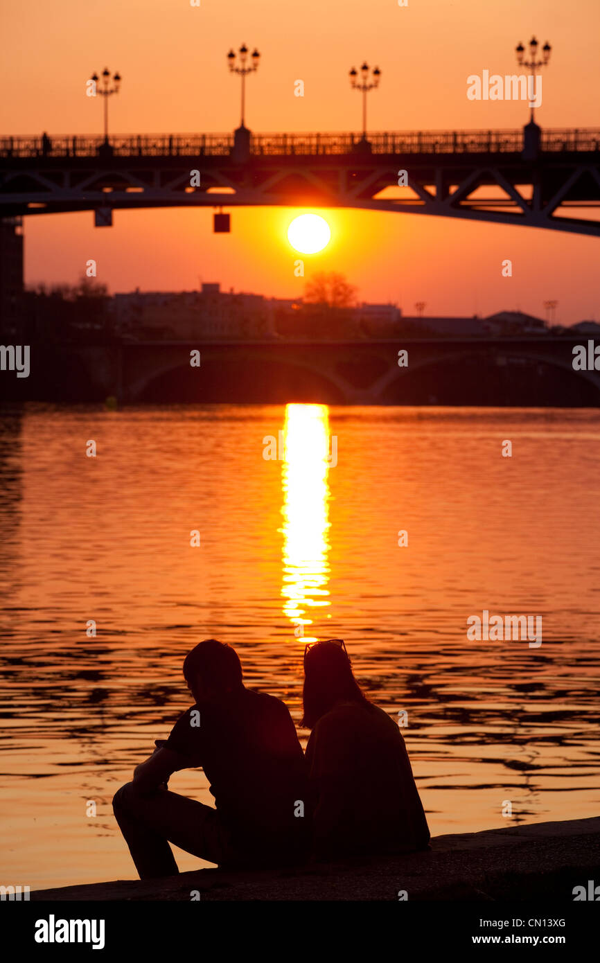 Couple watching sunset behind the Pont St. Pierre, river Garonne, Toulouse, France - Stock Image