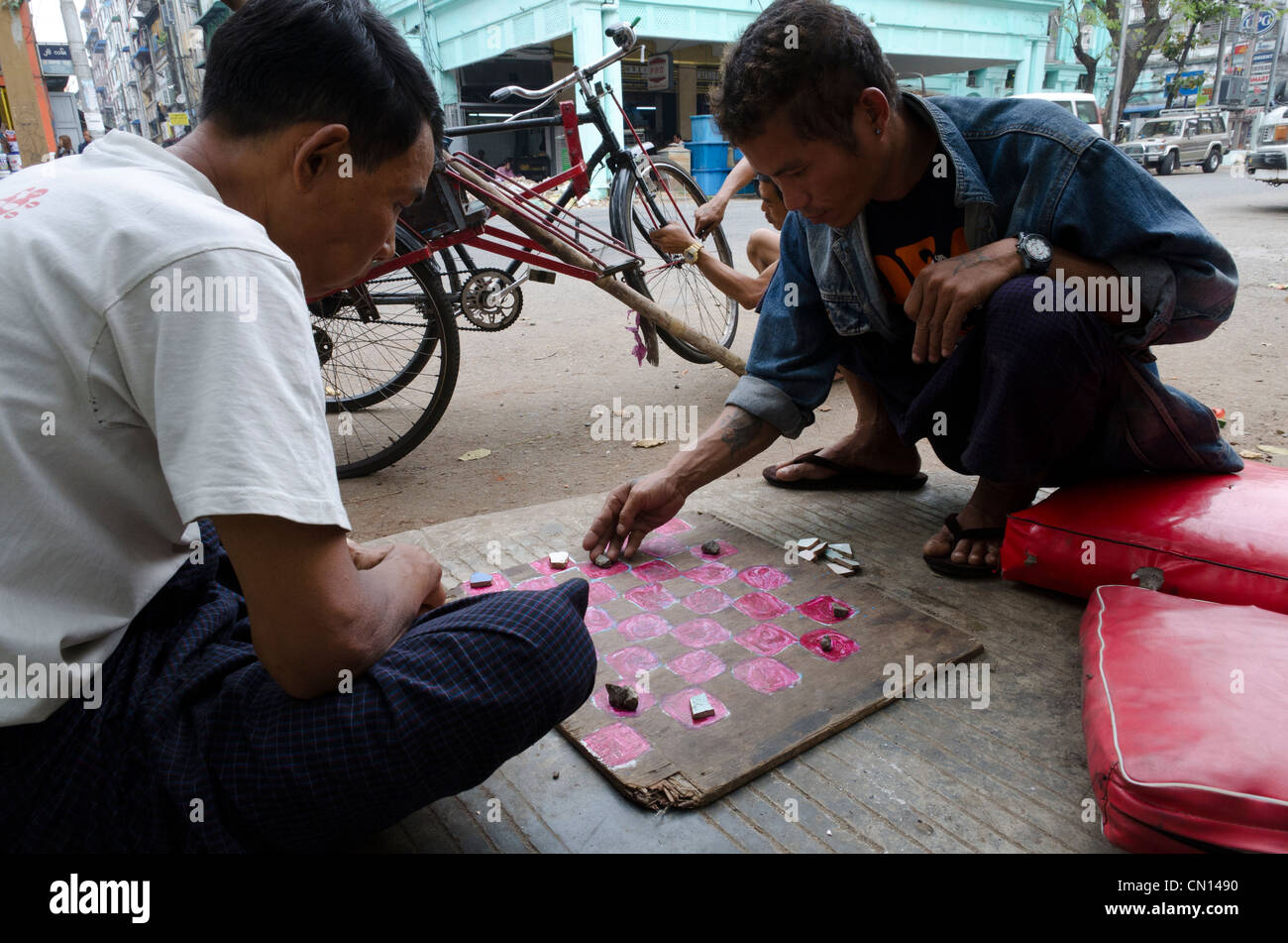 Trishaw drivers playing checkers in the streets of Yangon. Myanmar. Stock Photo