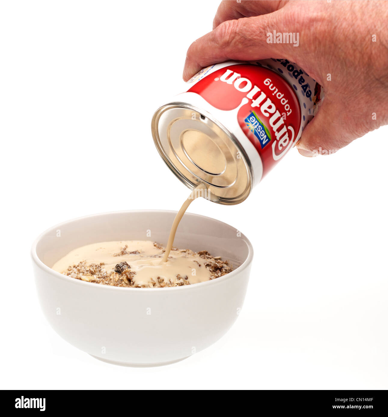 Tin of Carnation topping cream pouring onto a dish of muesli - Stock Image