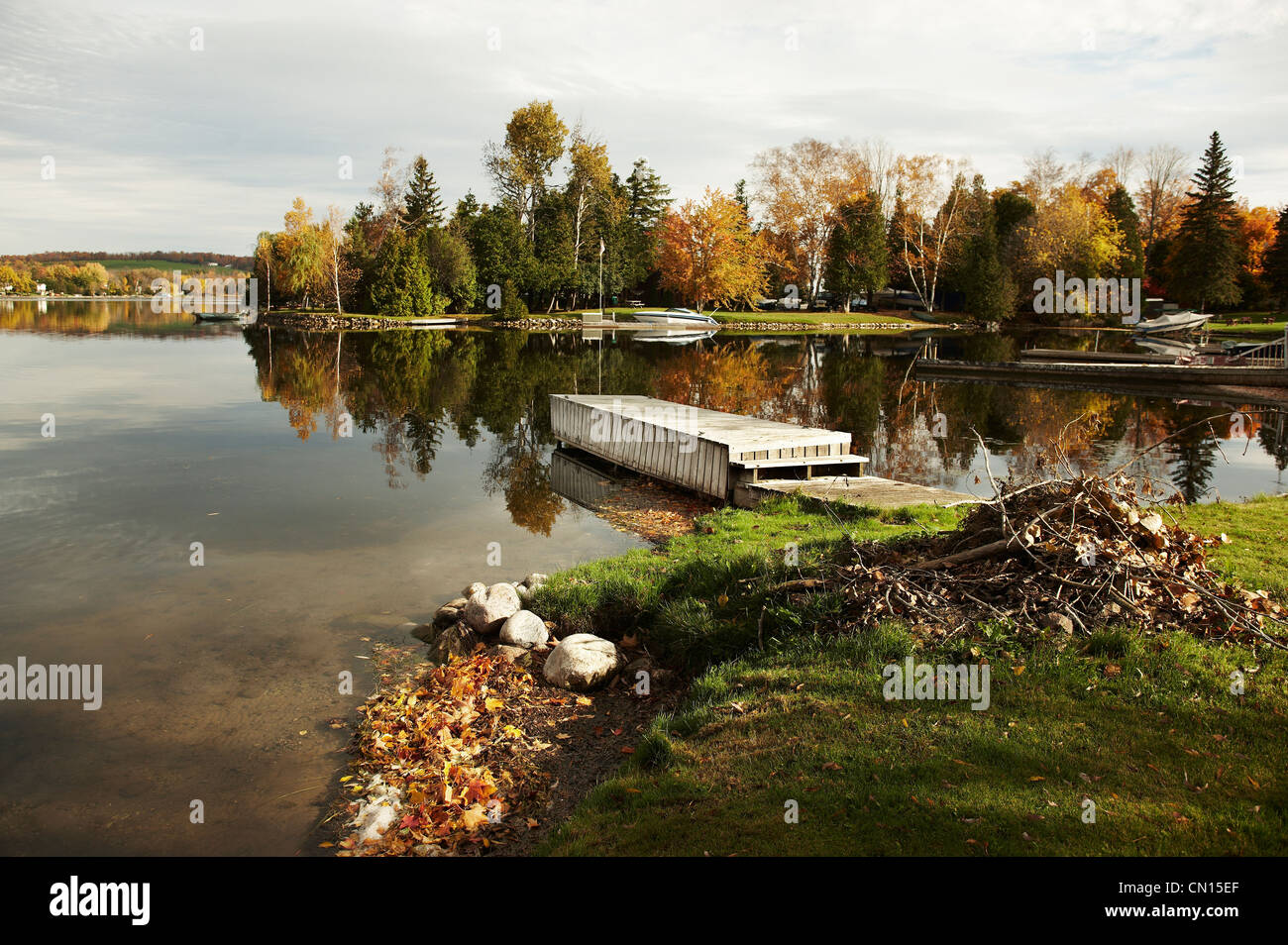 A dock on a lake in cottage country in fall, Peterborough, Ontario - Stock Image