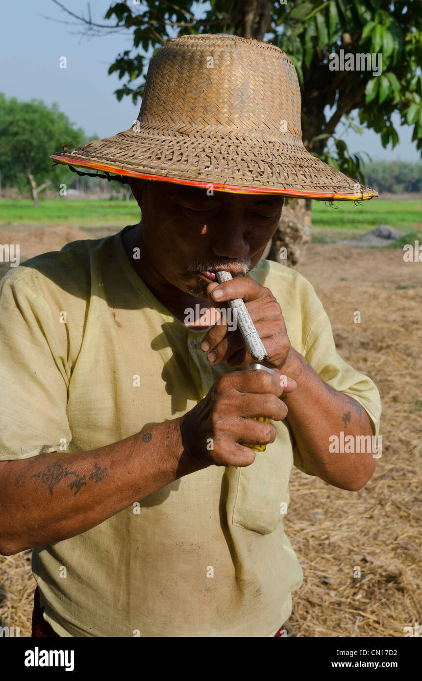 Portrait of a farmer with home made cigar. Myaungma. Irrawaddy delta. Myanmar. - Stock Image