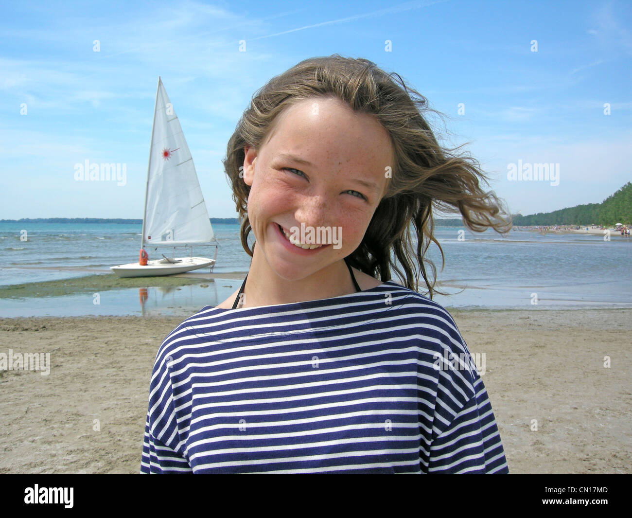 Portrait of young girl on beach with sailboat in background, Sandbanks Provincial Park, Prince Edward County, Ontario - Stock Image