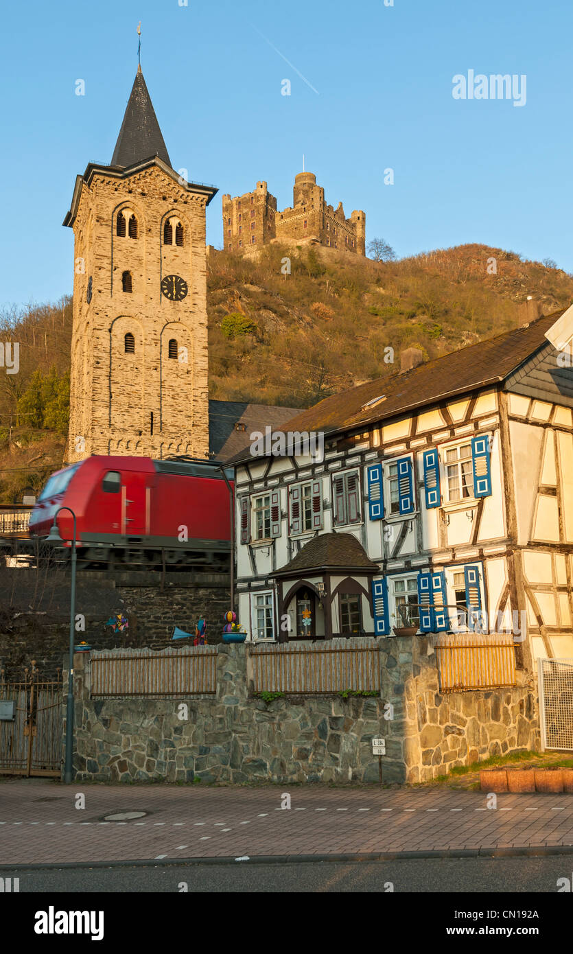 Freight train passing through the village of Wellmich below Burg Maus  in UNESCO listed 'Upper Middle Rhine - Stock Image