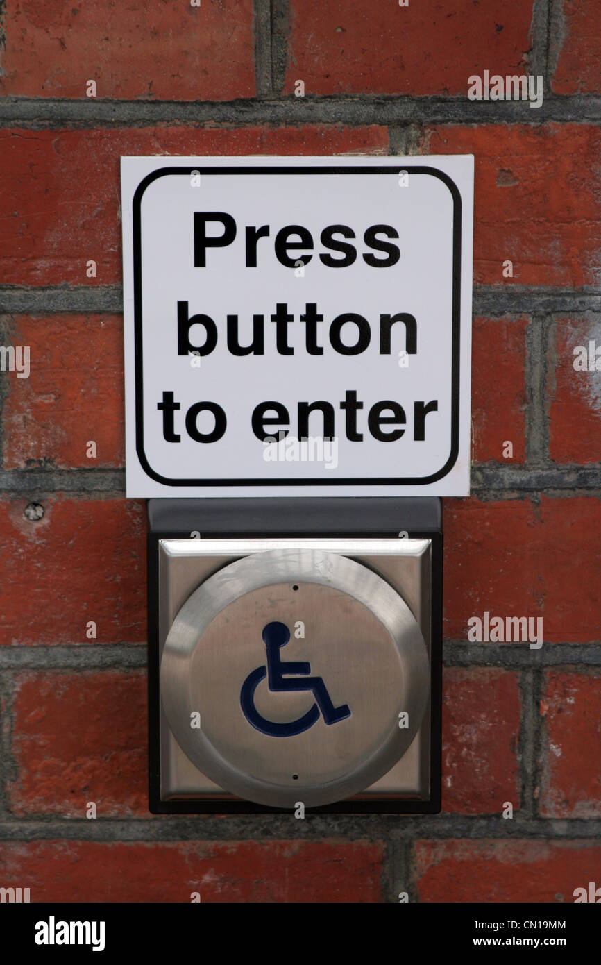 'Press button to enter' sign for disabled people, at a train station in England, UK - Stock Image