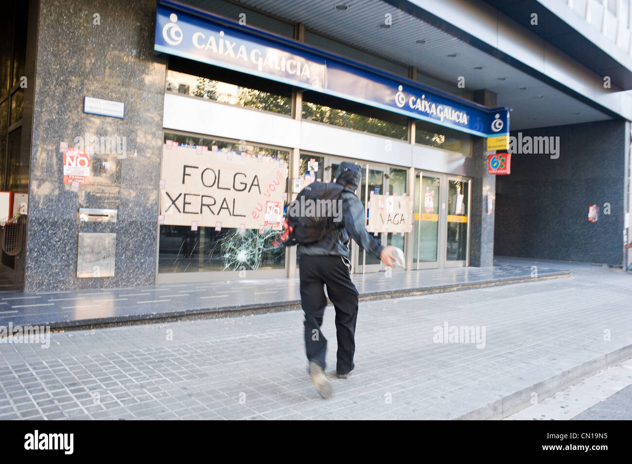 Protestor attacking a bank branch during the general strike of 2010 in Barcelona, Spain. - Stock Image