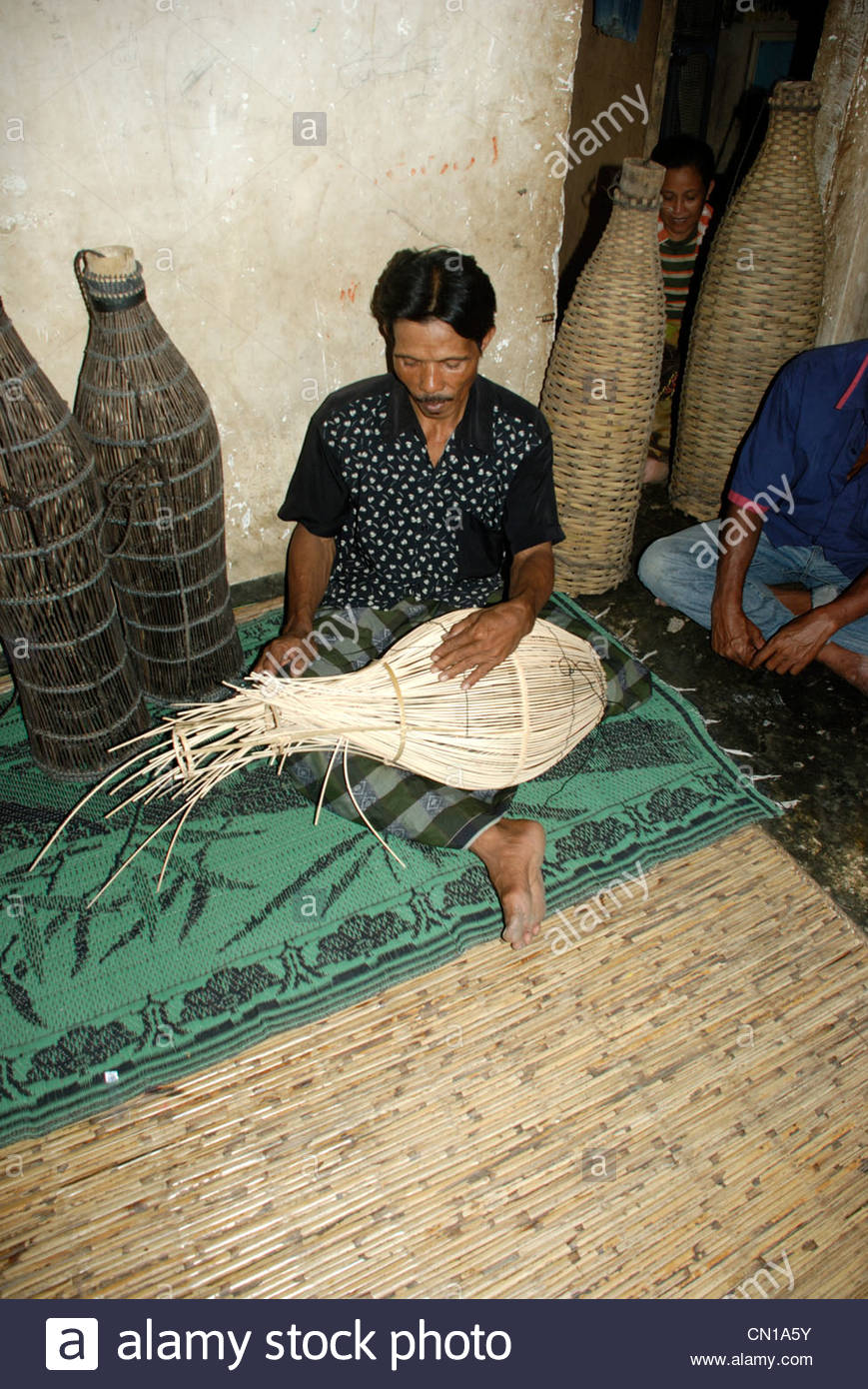 Man seated on mat e house making fish traps from cane and bamboo and arenga palm Cakranegara Lombok Barat NTB Indonesia Stock Photo