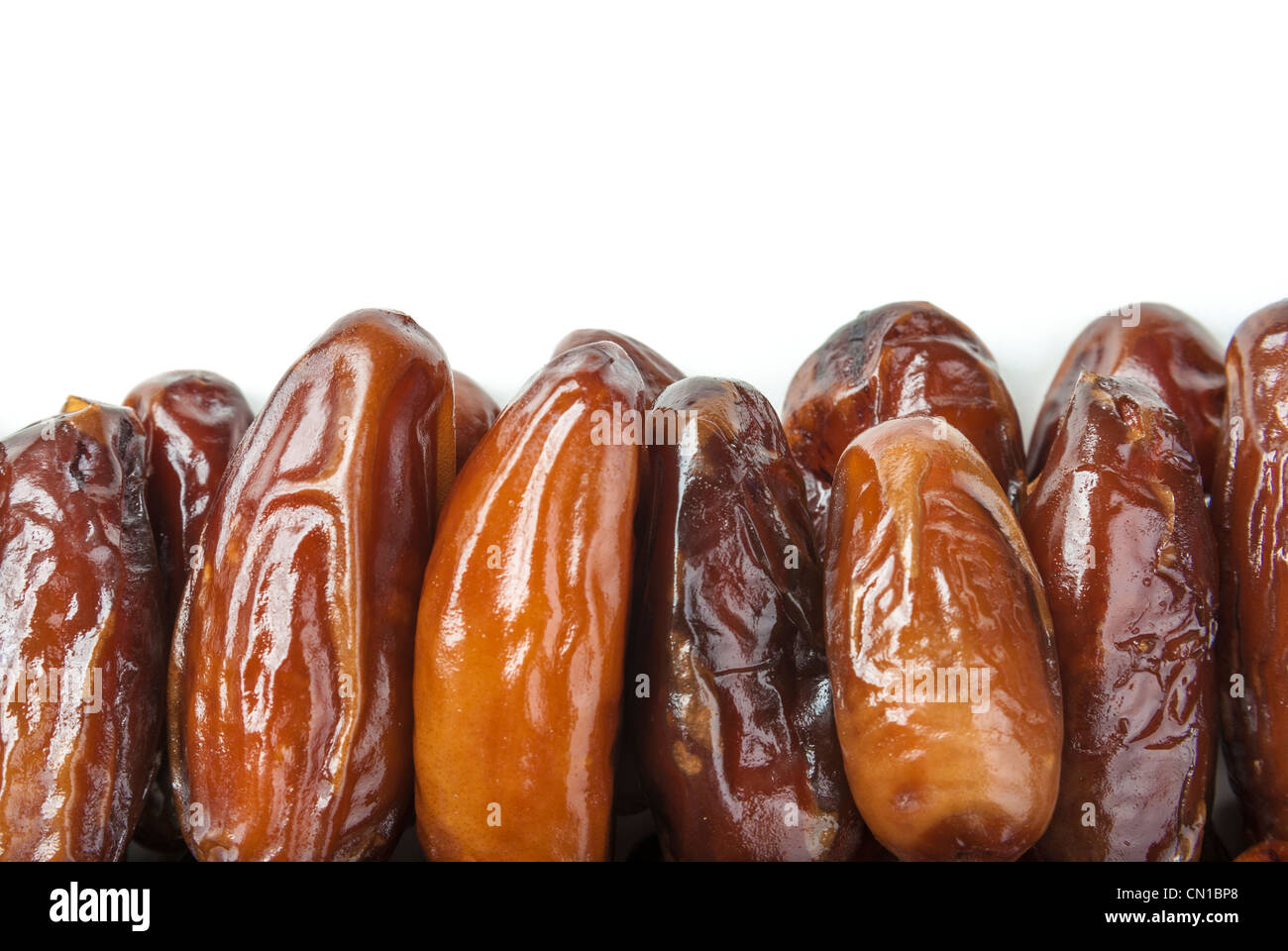 A stack of delicious date fruits on a white background - Stock Image