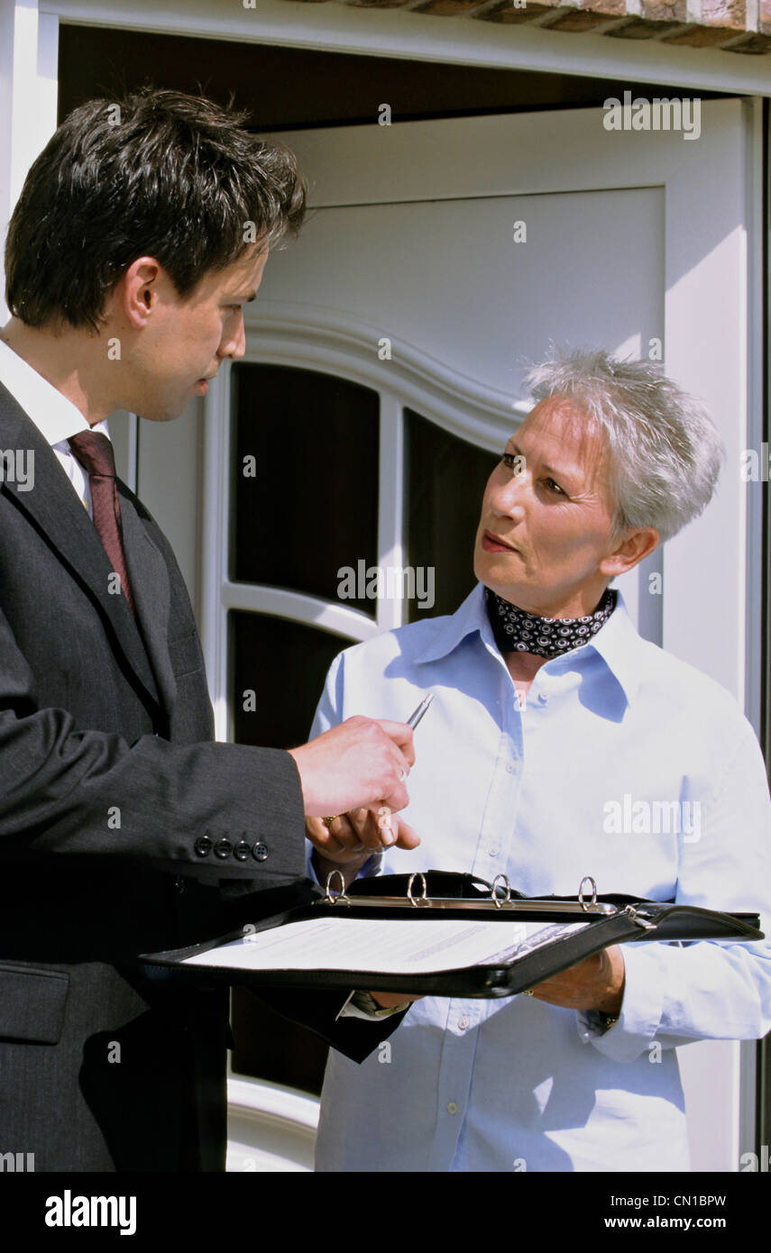 Woman with agent in front of the door - Stock Image