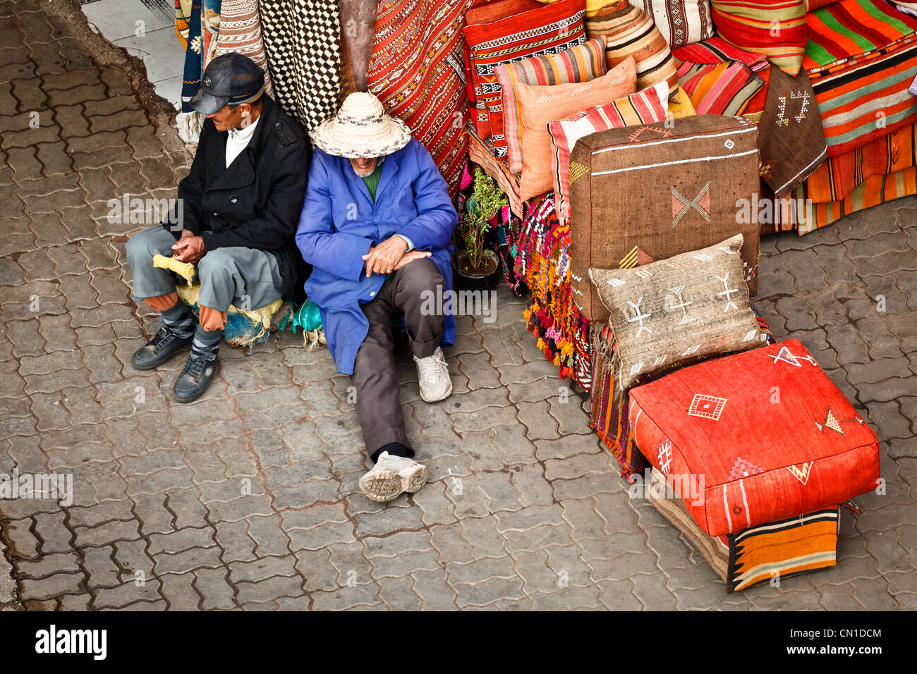 Two men resting on a pile of carpets in the Souk, Medina, Marrakech, Morocco, - Stock Image