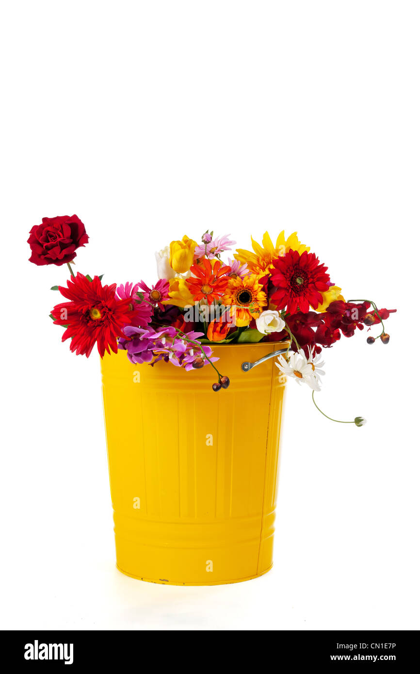 Yellow trash can full with silk flowers - Stock Image
